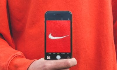 A photograph of someone taking a cell phone photo of the nike swoosh against a red background.