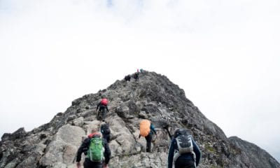 Mountain climbers reaching the peak of a rocky mountain.