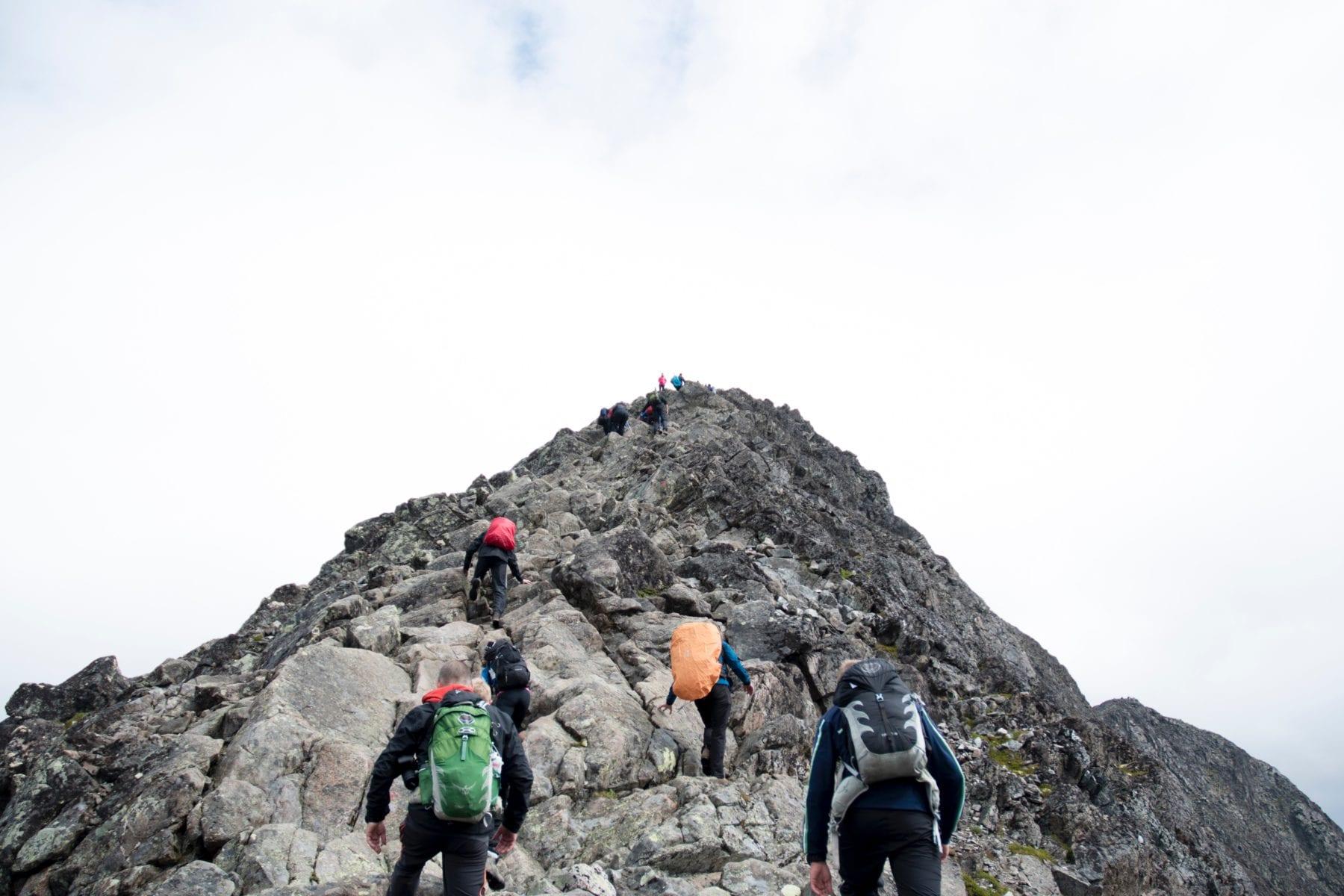 Mountain climbers reaching the peak of a rocky mountain.