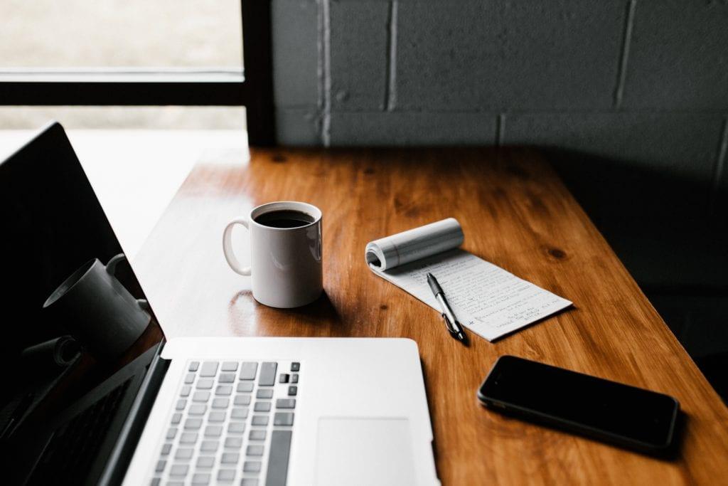 laptop, smartphone, notepad, and coffee mug on desk near window