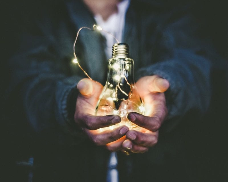 light bulb surrounded by string lights held in man's hand