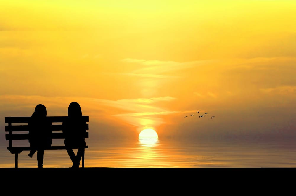A person giving advice on a bench at sunset.