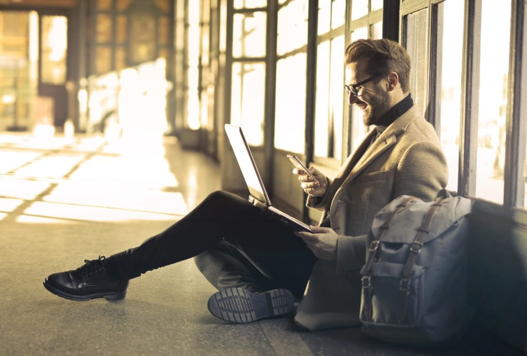 man with laptop and cell phone sitting down and smiling
