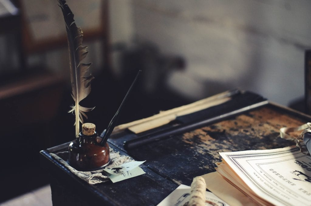 quill and ink on a wooden table with a stack of papers